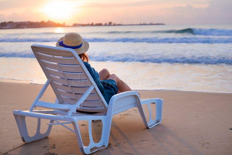 Красивая девушка в шляпе сидит на deckchair встречая рассвет стоковые фото