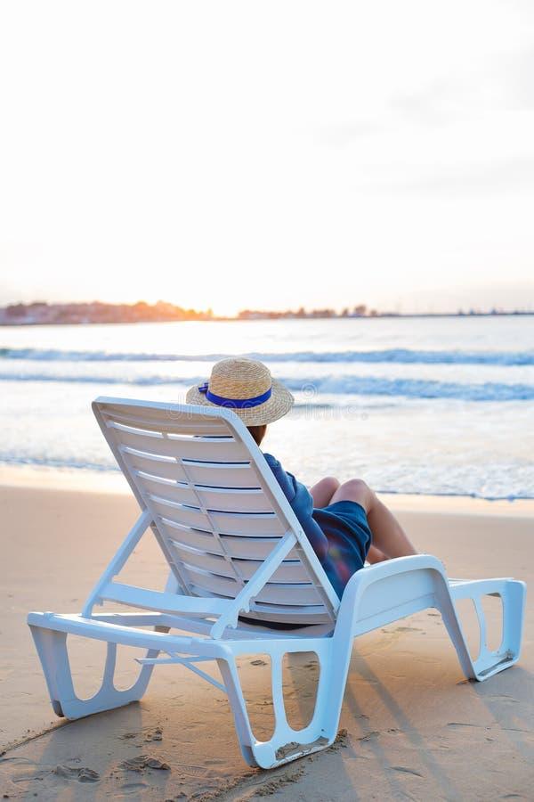 Красивая девушка в шляпе сидит на deckchair встречая рассвет стоковое фото rf