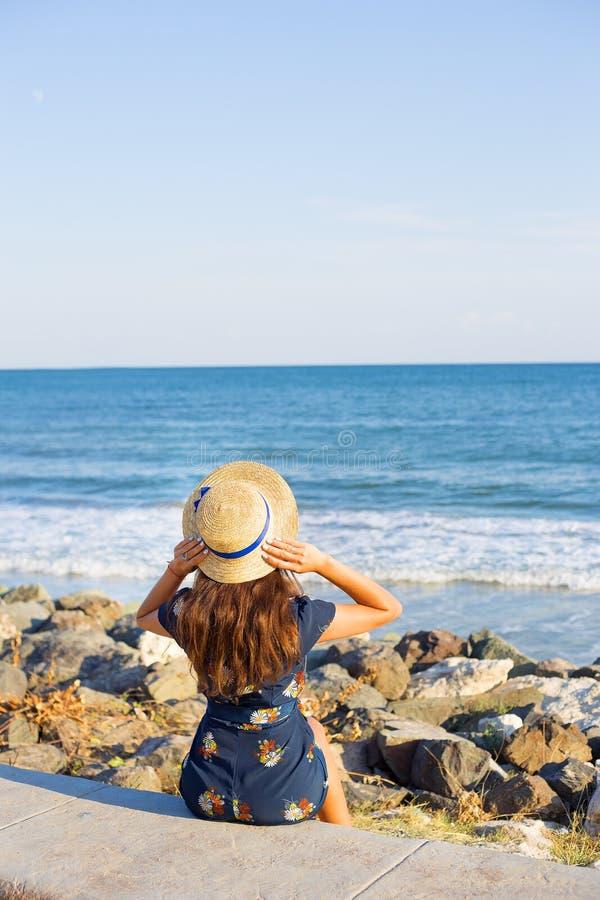 Красивая девушка в шляпе сидит около моря на камнях стоковое фото rf