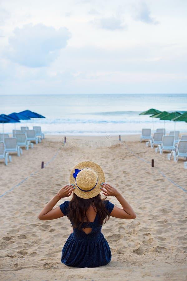Красивая девушка в шляпе сидит с ей назад на песчаном пляже стоковая фотография
