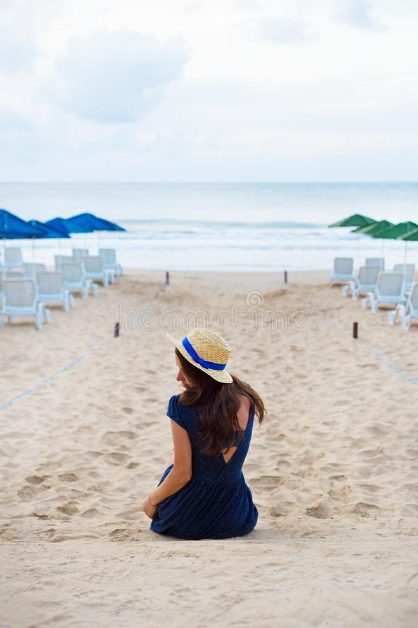 Красивая девушка в шляпе сидит с ей назад на песчаном пляже стоковое фото rf