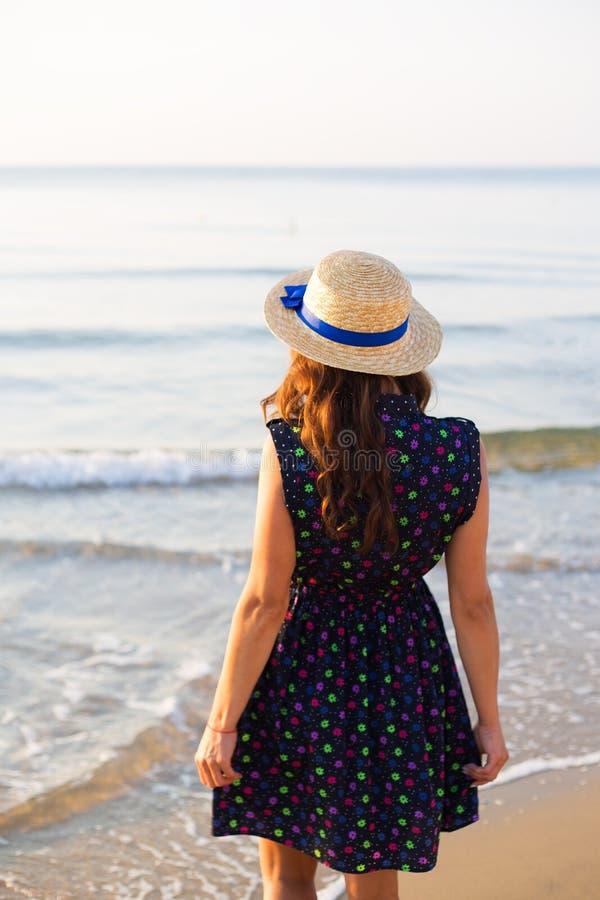 Красивая девушка в шляпе стоит с ей назад на песчаном пляже стоковые фотографии rf