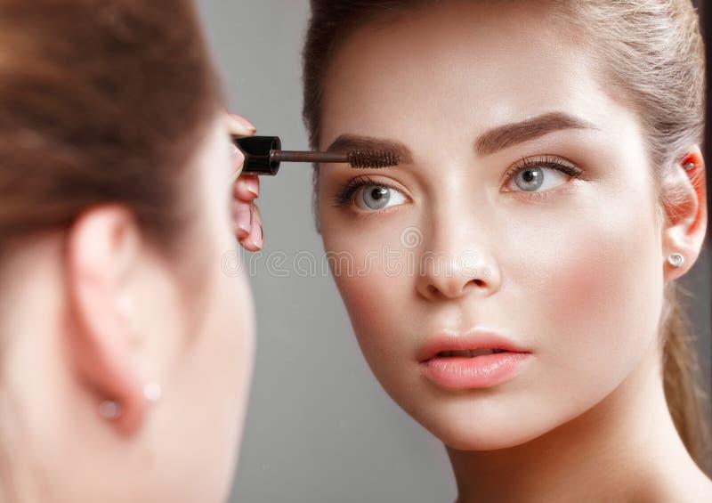 Красивая девушка делает состав в зеркале Сторона красотки стоковая фотография