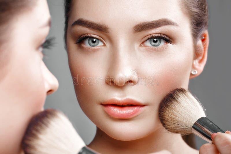 Красивая девушка делает состав в зеркале Сторона красотки стоковое фото rf