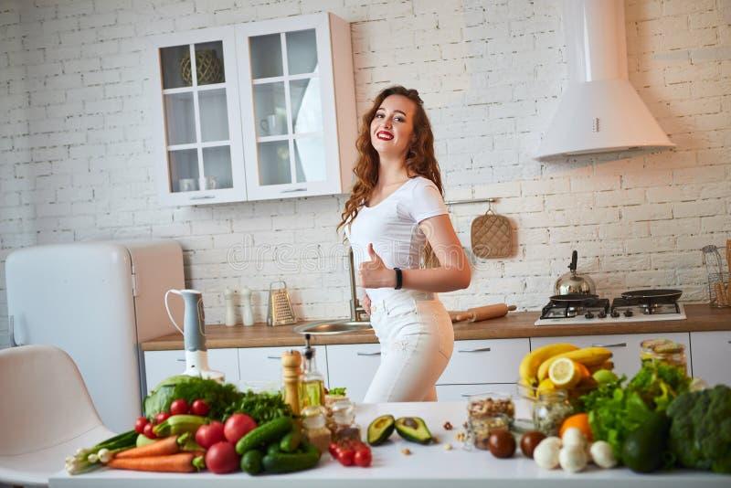 Красивая девушка демонстрирует ее идеальную диаграмму и показывать большие пальцы руки вверх на фоне здоровой еды в кухне стоковое фото rf