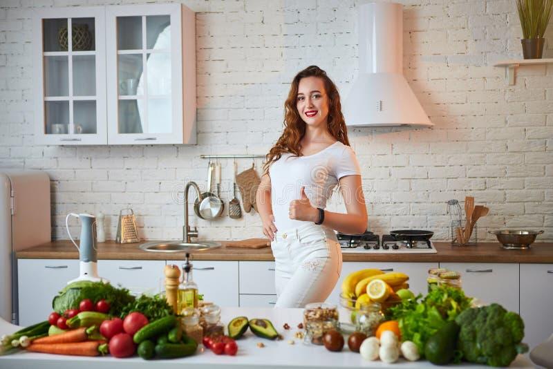 Красивая девушка демонстрирует ее идеальную диаграмму и показывать большие пальцы руки вверх на фоне здоровой еды в кухне стоковые фотографии rf