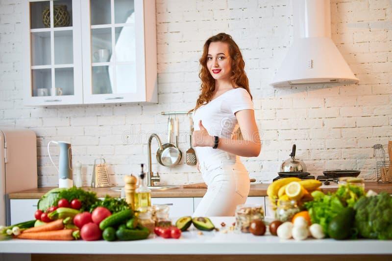 Красивая девушка демонстрирует ее идеальную диаграмму и показывать большие пальцы руки вверх на фоне здоровой еды в кухне стоковое фото