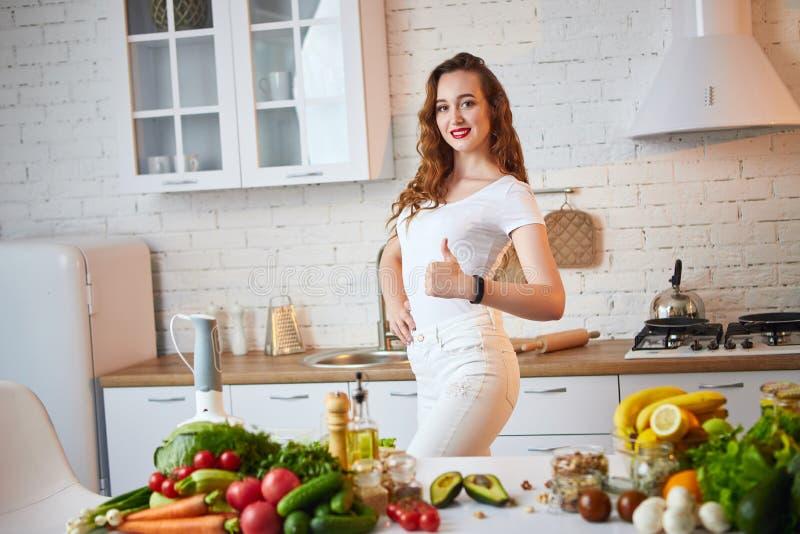 Красивая девушка демонстрирует ее идеальную диаграмму и показывать большие пальцы руки вверх на фоне здоровой еды в кухне стоковое изображение