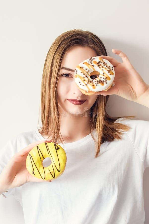 Красивая девушка держа donuts стоковое изображение
