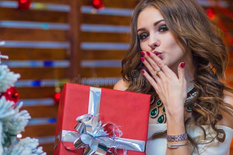 Красивая девушка держит красную подарочную коробку и посылает поцелуй воздуха стоковое фото