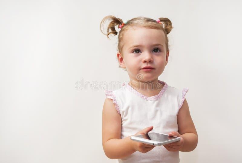 Красивая девушка играя и касаясь мобильный телефон стоковые фотографии rf