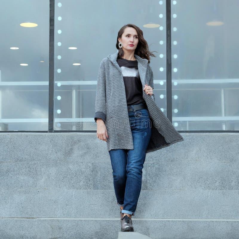Красивая девушка идет через город Стильный брюнет в пальто и джинсах идет вперед r Demi рекламы моды стоковое фото rf