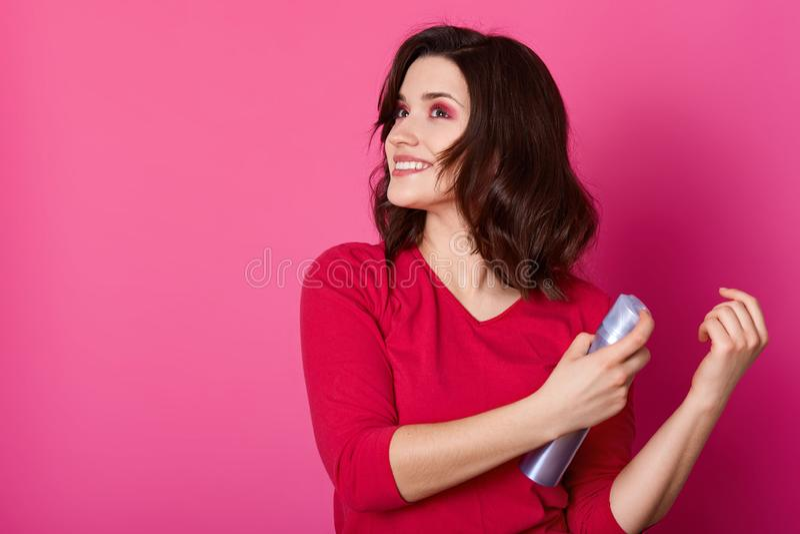 Красивая девушка кладя починки используя спрея для волос, подготавливает для датировать с парнем, делает новую прическу Брюнет Sm стоковые фотографии rf
