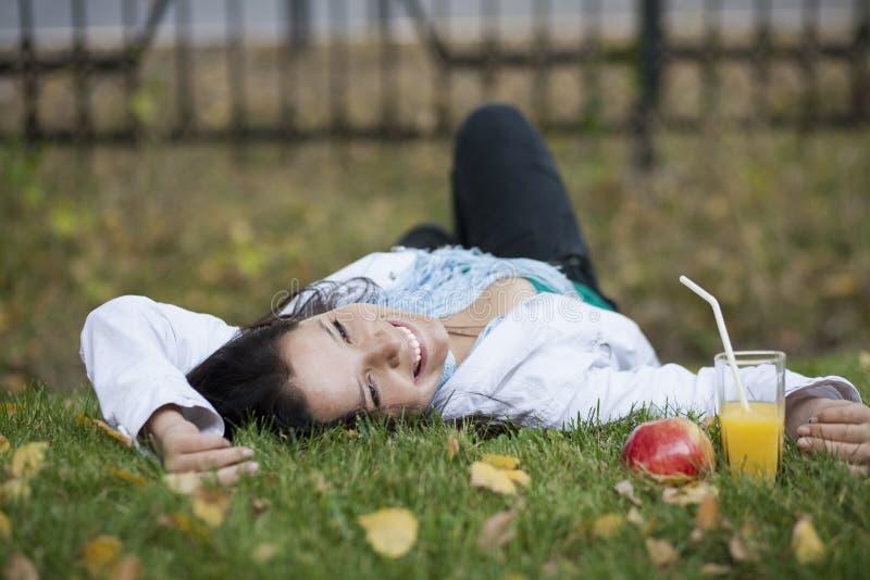 Красивая девушка лежа на траве стоковое фото