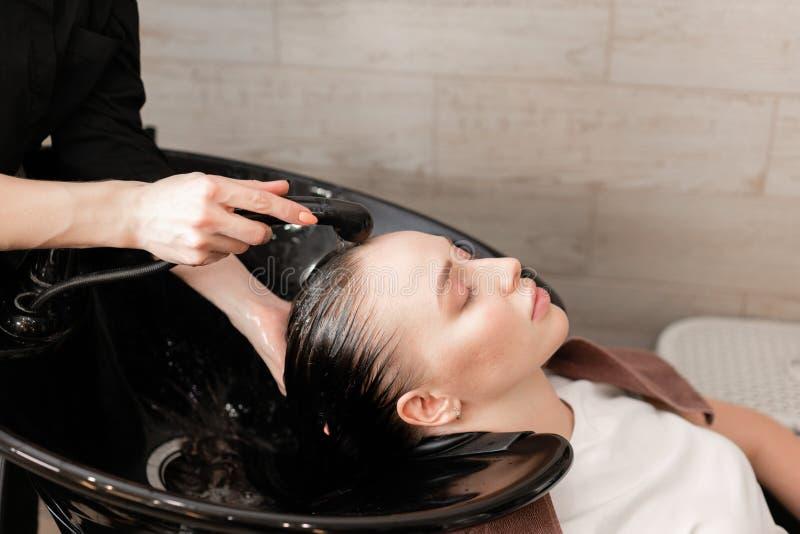 Красивая девушка моет ее волосы перед стрижкой в салоне красоты стирка волос на парикмахерских услугах профессиональный шампунь стоковое фото rf