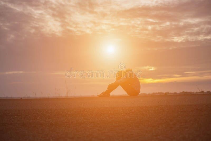 Красивая девушка наблюдая красивый заход солнца на воде стоковые изображения