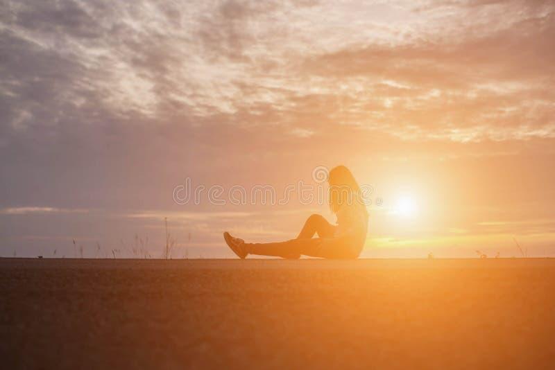 Красивая девушка наблюдая красивый заход солнца на воде стоковое фото