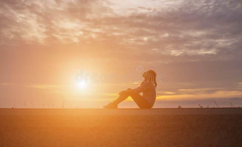 Красивая девушка наблюдая красивый заход солнца на воде стоковое изображение rf