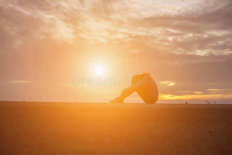 Красивая девушка наблюдая красивый заход солнца на воде стоковое фото rf