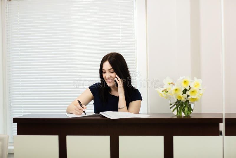 Красивая девушка на приемной отвечая звонку в зубоврачебном офисе стоковая фотография rf