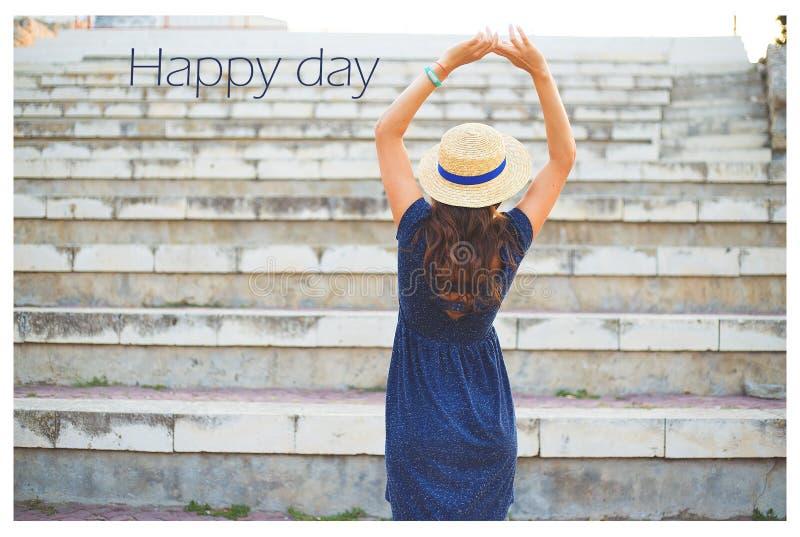 Красивая девушка на шагах в голубой день платья и шляп-надписи счастливый стоковые фотографии rf