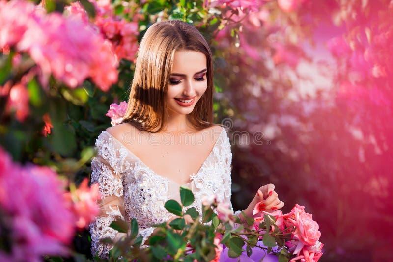 Красивая девушка нося элегантное платье представляя около красочных цветков Произведение искусства романтичной женщины стоковая фотография rf