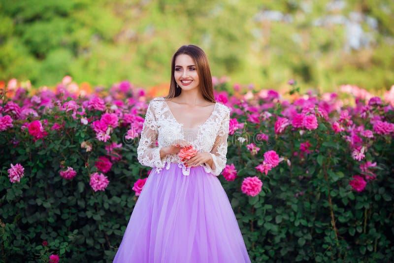 Красивая девушка нося элегантное платье представляя около красочных цветков Произведение искусства романтичной женщины стоковые изображения