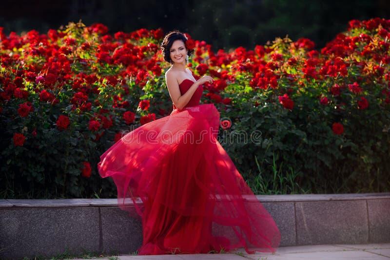 Красивая девушка нося элегантное платье представляя около красочных цветков Произведение искусства романтичной женщины стоковое изображение