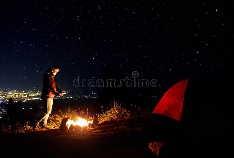 Красивая девушка около лагерного костера на звездной ночи стоковое изображение rf