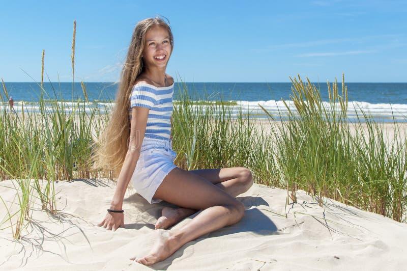 Красивая девушка отдыхая на пляже стоковое фото rf