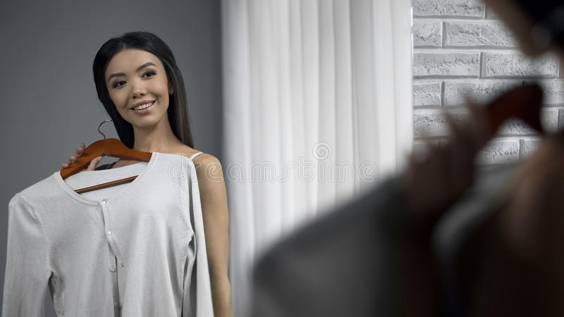 Красивая девушка проверяя как блузки смотрят на ей перед зеркалом, одежды стоковое фото rf