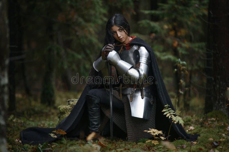 Красивая девушка ратника с chainmail шпаги нося и панцырь в загадочном лесе