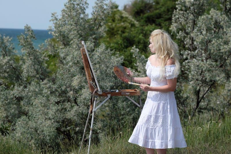 Красивая девушка рисует изображение в парке используя палитру с красками Мольберт и холст с изображением стоковые фото
