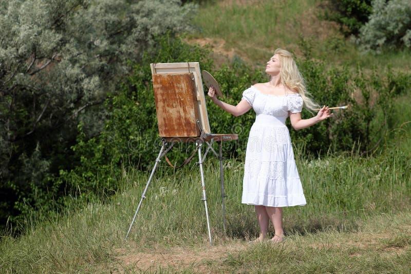 Красивая девушка рисует изображение в парке используя палитру с красками Мольберт и холст с изображением стоковое изображение rf