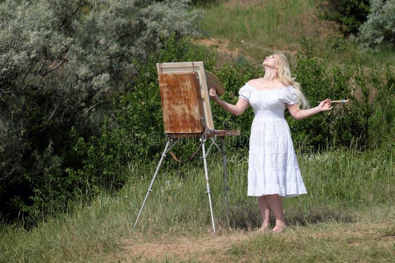 Красивая девушка рисует изображение в парке используя палитру с красками Мольберт и холст с изображением стоковое изображение
