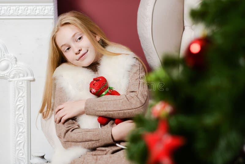 Красивая девушка рождества обнимая игрушку сидя в белом стуле около камина и рождественской елки стоковые фото