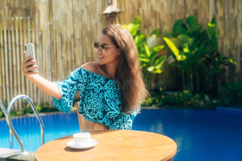 Красивая девушка сидит outdoors на таблице с чашкой чаю или кофе и пользы знонят по телефону, делают selfie стоковое фото rf