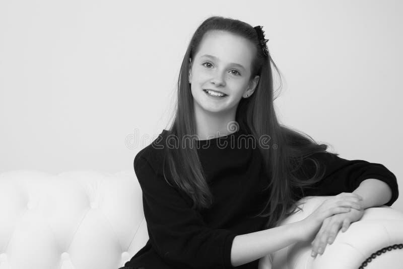 Красивая девушка, сидящая на диване у камина стоковые фото