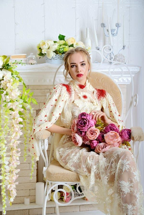 Красивая девушка сидя и представляя на винтажной табуретке в студии с букетом цветков в его руках и взглядах на мне стоковые фотографии rf