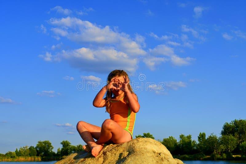 Красивая девушка сидя на большом утесе Маленькая девочка носит купальник Девушка делает сердце сформировать жест ее руками стоковое изображение rf