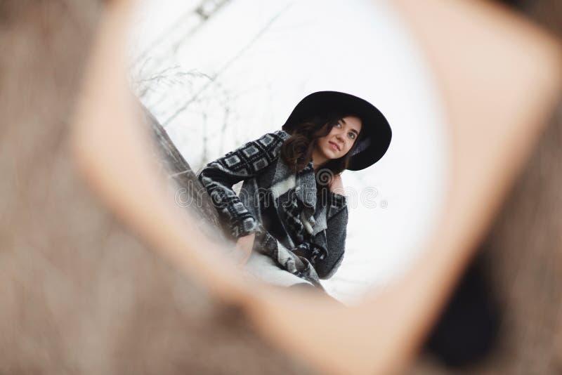 Красивая девушка сидя на деревянной доске Отражение в зеркале стоковое фото rf