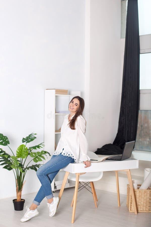 Красивая девушка сидя на столе в офисе и усмехаться Положительный молодой менеджер работая на проекте дела в офисе Busine стоковое фото