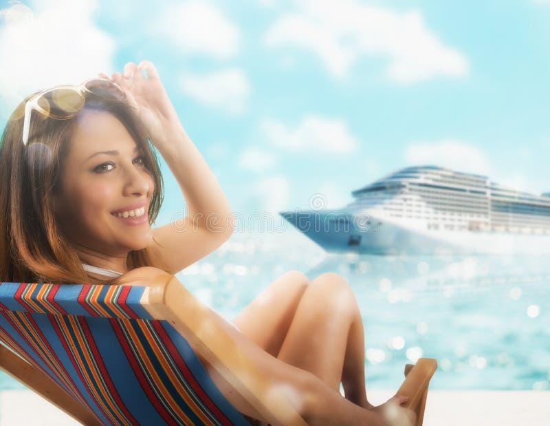 Красивая девушка сидя на шезлонге на пляже на заходе солнца с cruiseship на предпосылке стоковые изображения rf