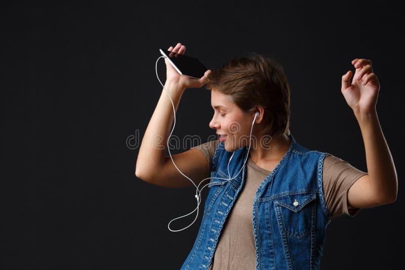 Красивая девушка слушает к музыке с ее телефоном на черной предпосылке стоковые изображения rf