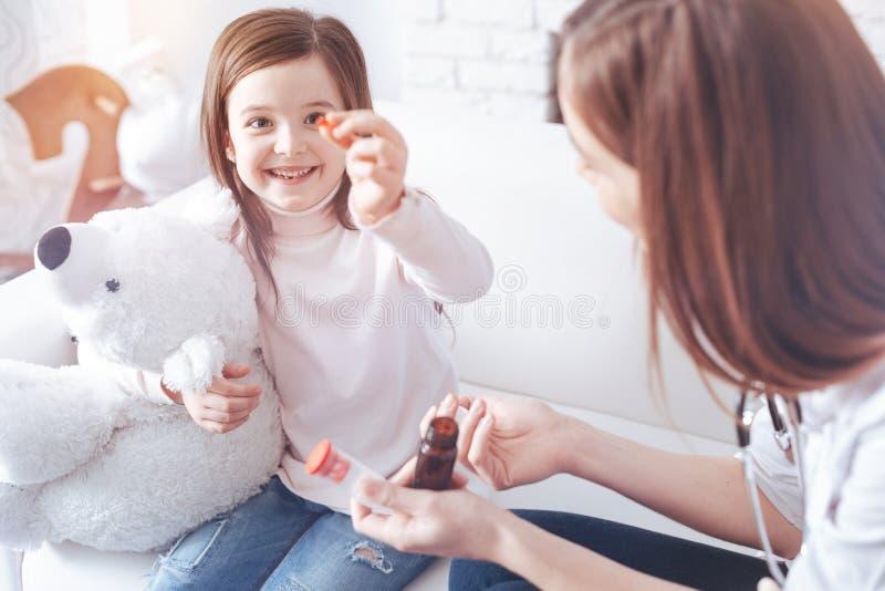 Красивая девушка смотря оранжевую пилюльку стоковое изображение rf