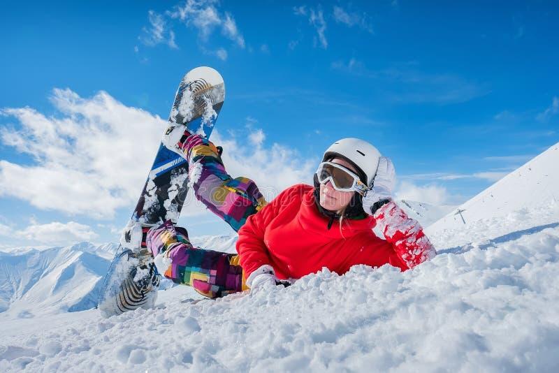 Красивая девушка сноуборда лежит на снеге смотря камеру стоковое изображение