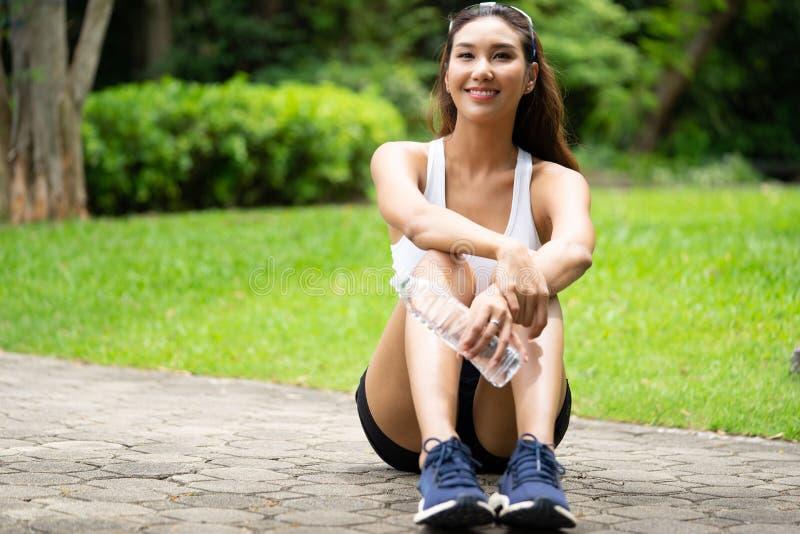 Красивая девушка спорта держа бутылку воды отдыхая после тренировки с стороной smiley, портретом женщины спорта стоковые фотографии rf