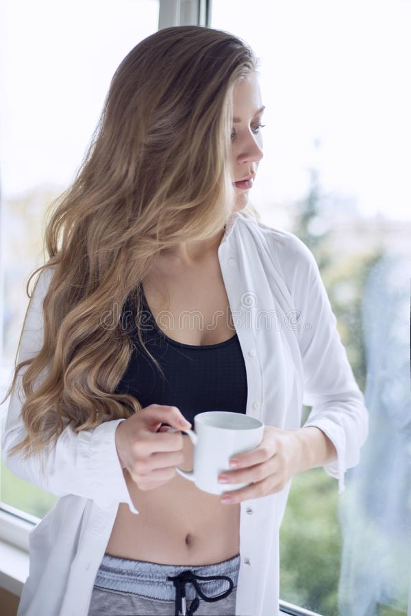 Красивая девушка спорт около окна с кружкой в руках стоковые изображения