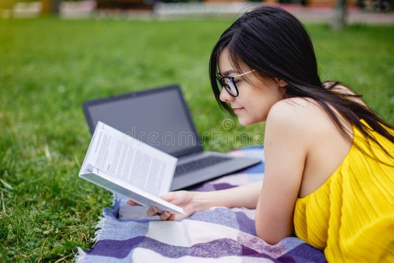 Красивая девушка студента прочитала книги и портативный компьютер на зеленой траве в парке в временени стоковая фотография rf