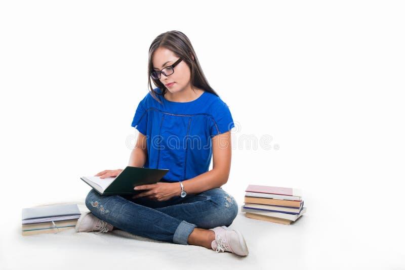 Красивая девушка студента сидя на одеяле и изучать стоковые изображения